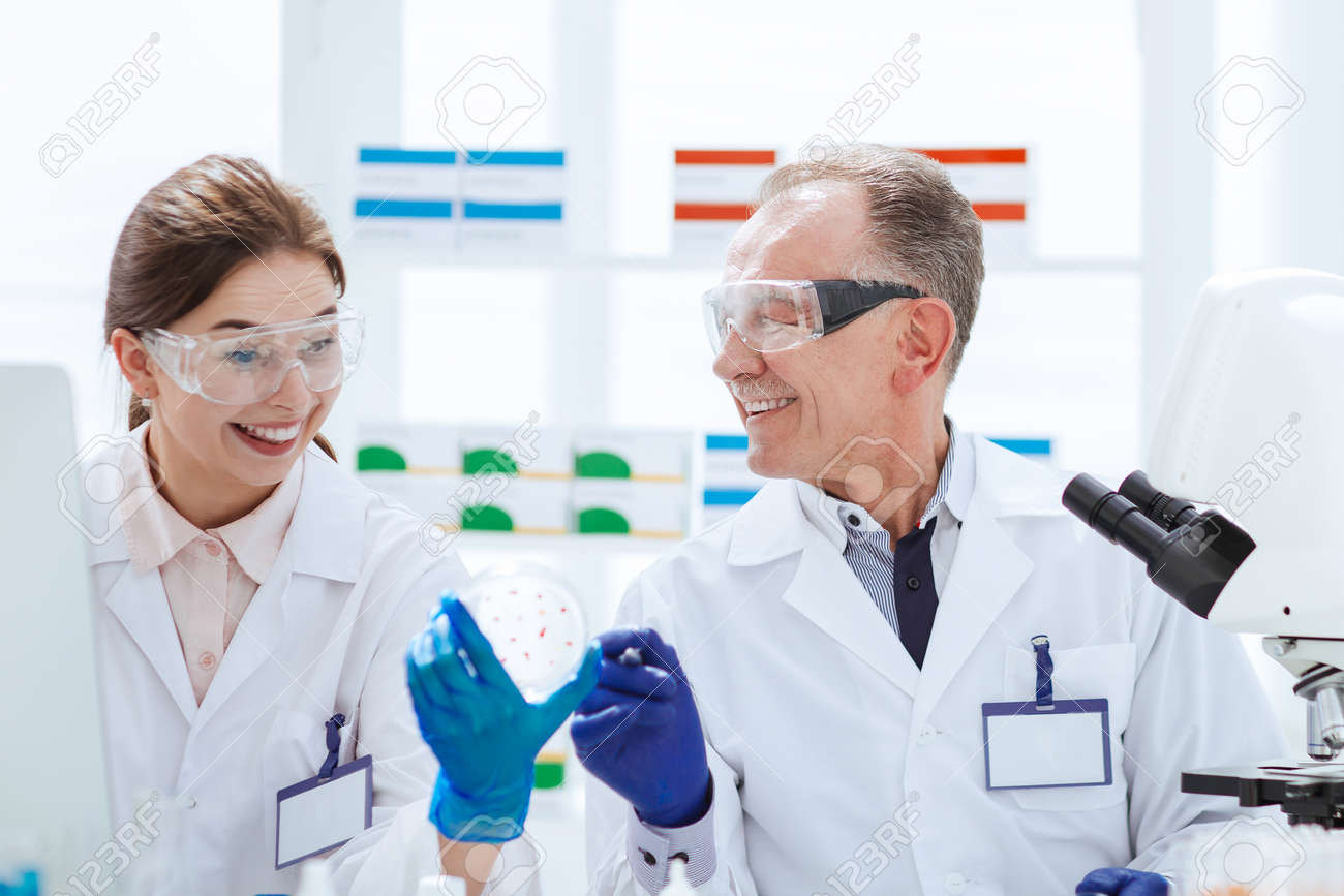 smiling scientists with a Petri dish sitting at a laboratory table. - 159918435