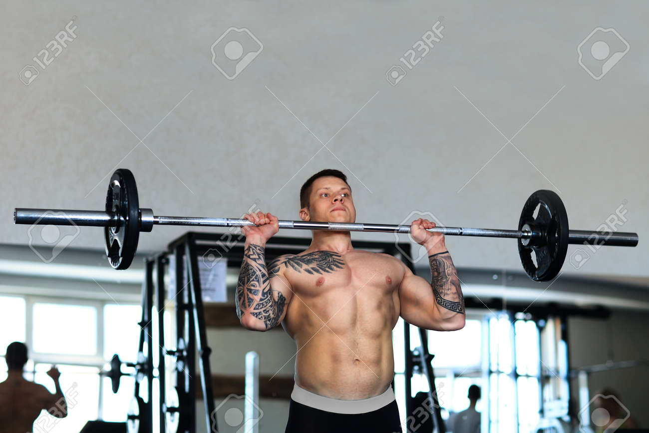 bodybuilder works with a barbell in the gym. - 165119553