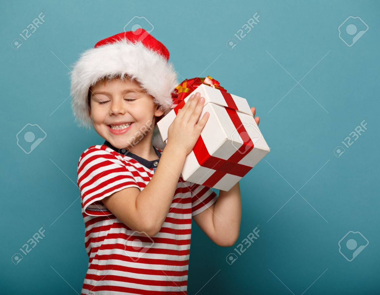 Smiling Funny Child In Santa Red Hat Holding Christmas Gift ...