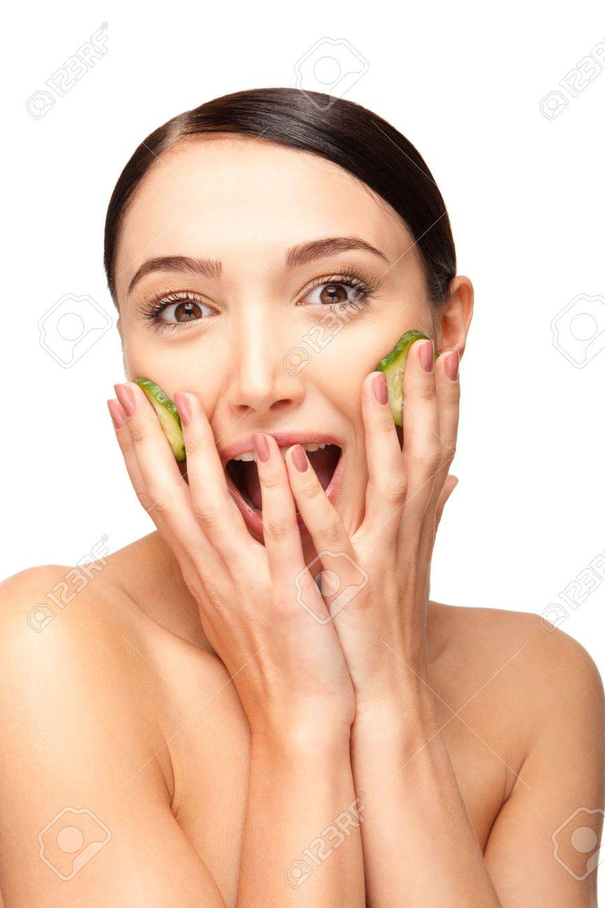 Close-up face of beautiful woman with clean fresh healthy skin and with cucumber slices around the cheeks. Isolated on white Stock Photo - 17344970