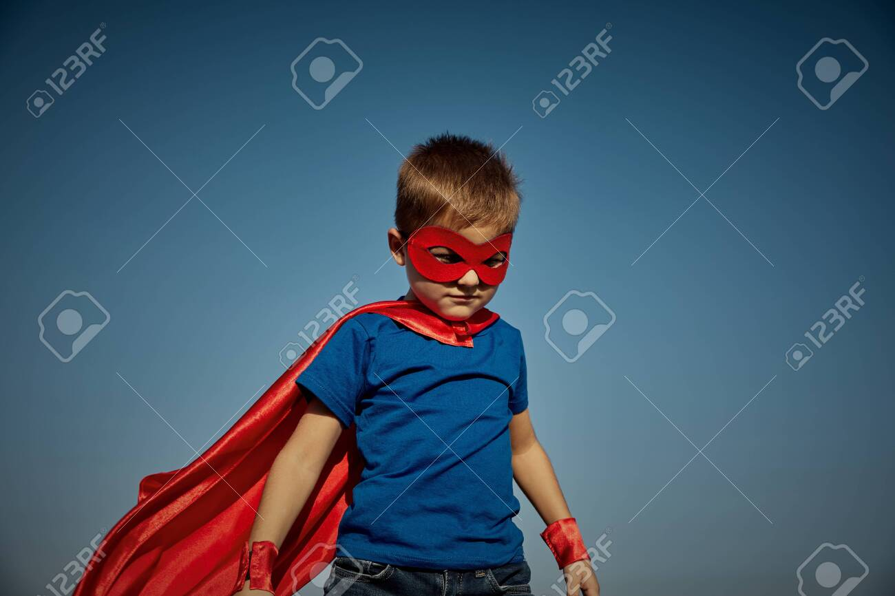 Funny little power super hero child (boy) in a red raincoat. Superhero concept - 136863110