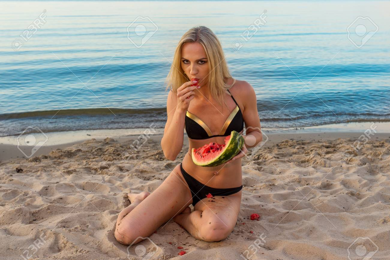 7c2577e34d0de closeup portrait of happy sexy girl in black bikini relaxing on the sand  with fruits against