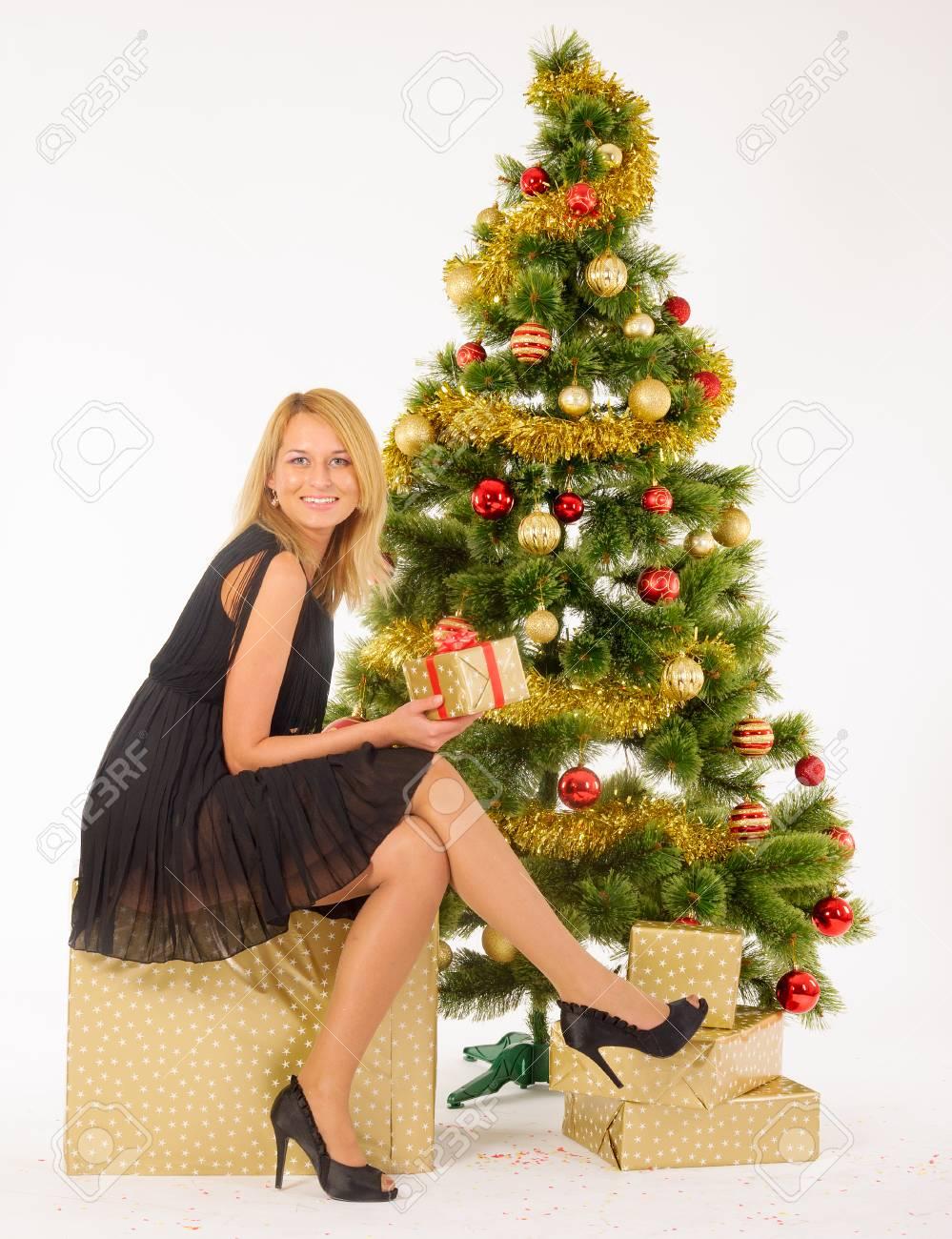 b18d58d81f Foto de archivo - Hermosa mujer posando cerca de árbol de Navidad