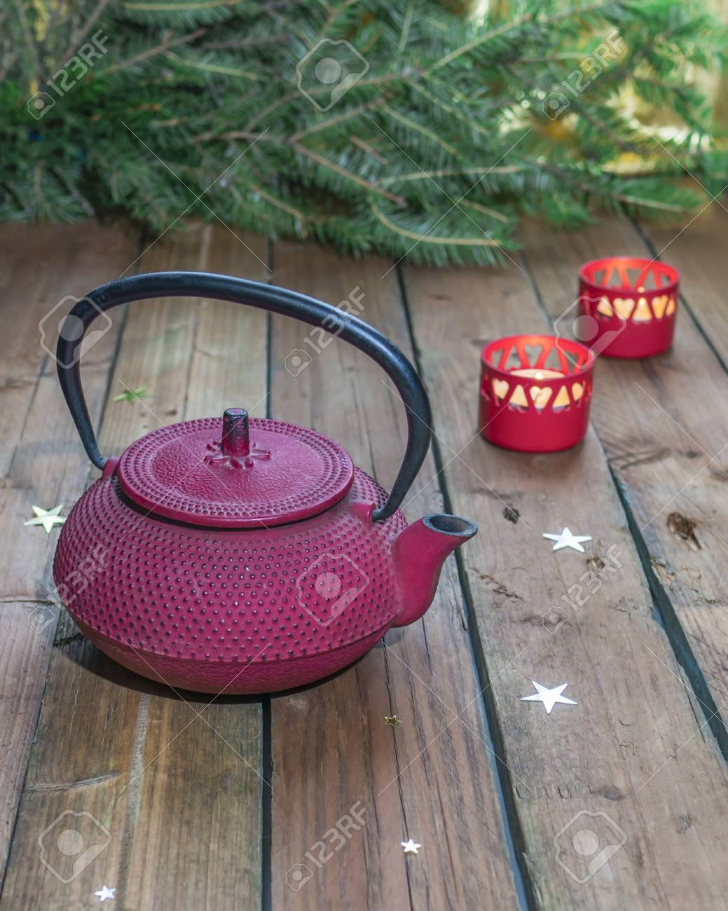 Red Cast Iron Chinese Teapot On A Background Of Christmas Candles