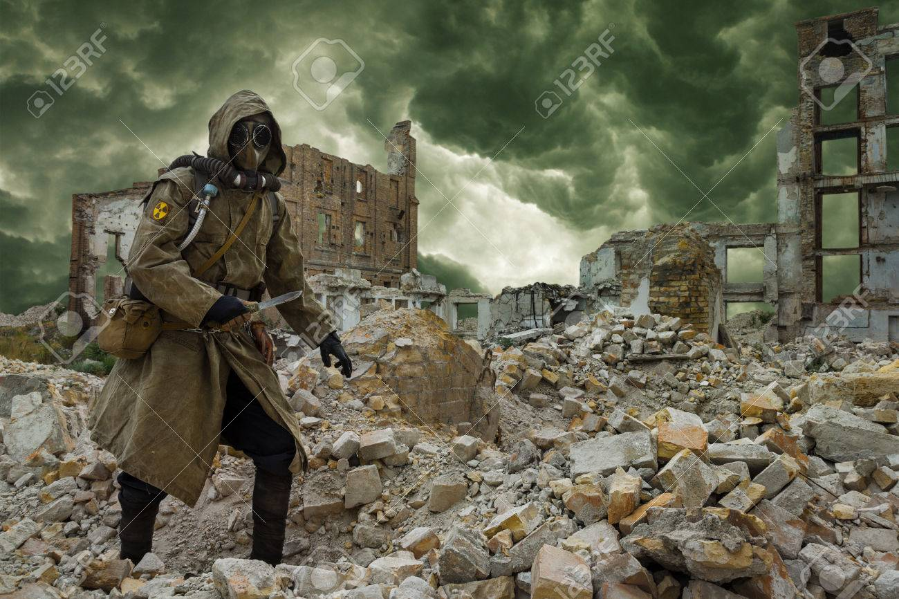 Post apocalypse. Sole survivor in tatters and gas mask on the ruins of the destroyed city - 50873370