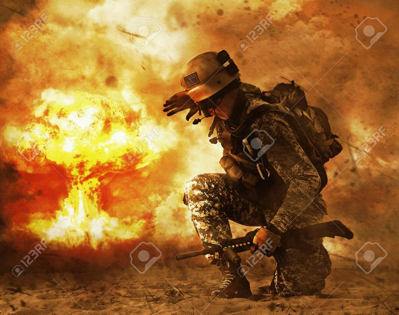 US soldier in the desert during the military operation turning to nuclear explosion mushroom cloud covering his eyes. He is doomed - 69805678