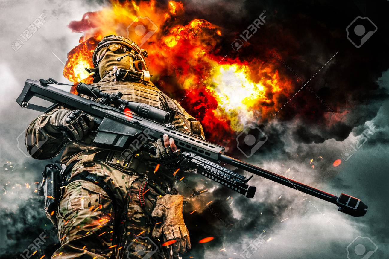 Army sniper of special forces in action posing with large caliber rifle. Heavy explosions, fire and smoke billowing on background. Low angle view - 79145773