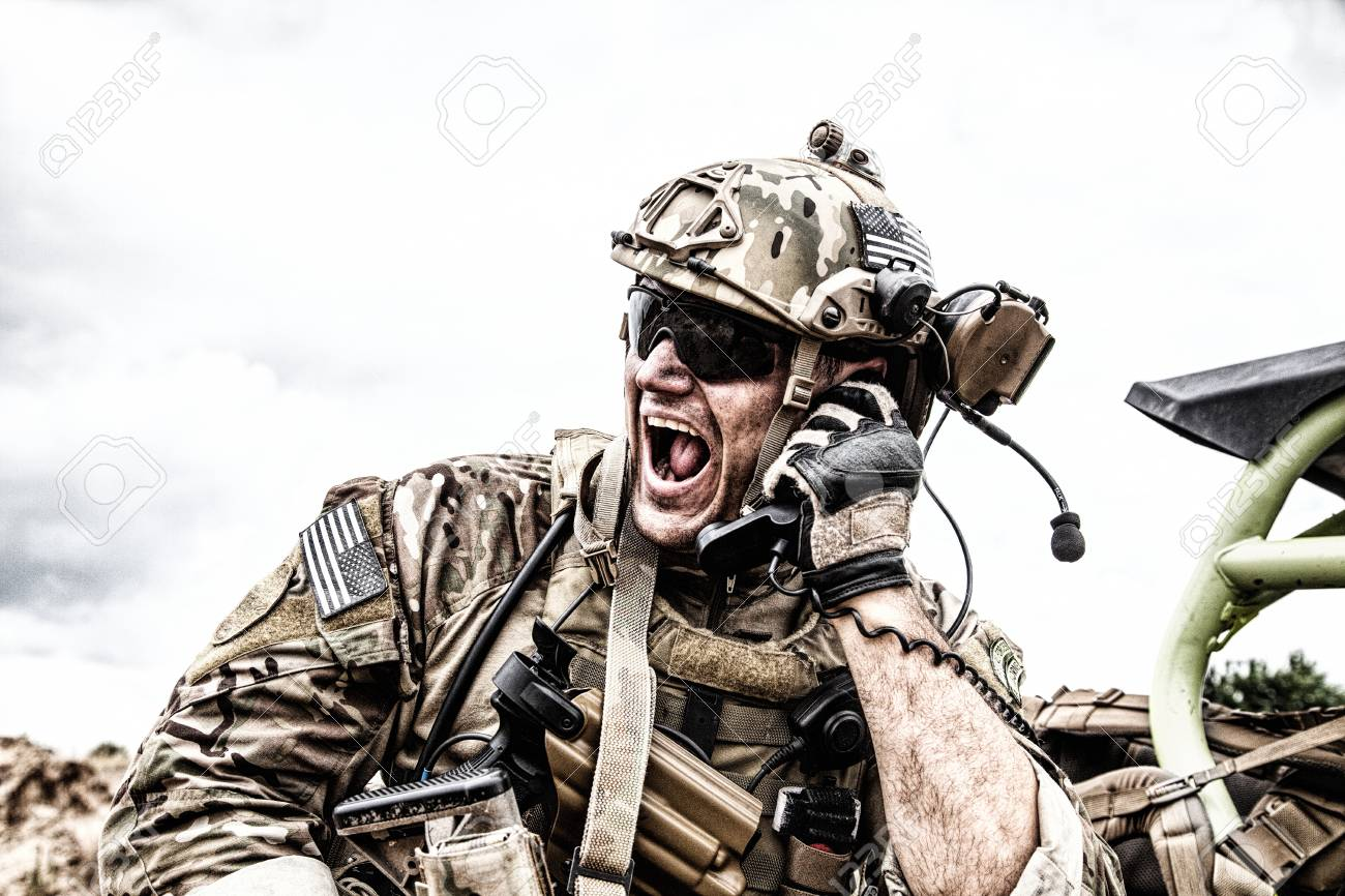 Special forces soldier, military communications operator or maintainer in helmet and glasses, screaming in radio during battle in desert. Calling up reinforcements, reporting situation on battlefield - 104627169