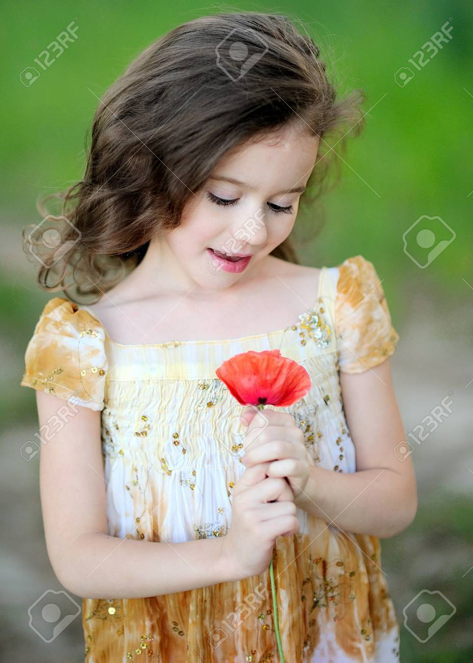 Portrait of Little girl with a flower poppy Stock Photo - 14186497