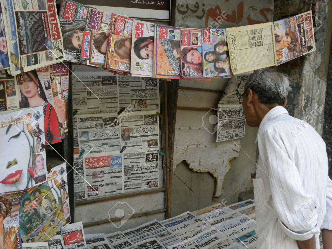PAKISTAN/KARACHI_LOCAL OLD MAN READING NEWS PAPER AT THE NEWS PAPER SHOP  TODAY ON TUSEDAY 27 MARCH 2012