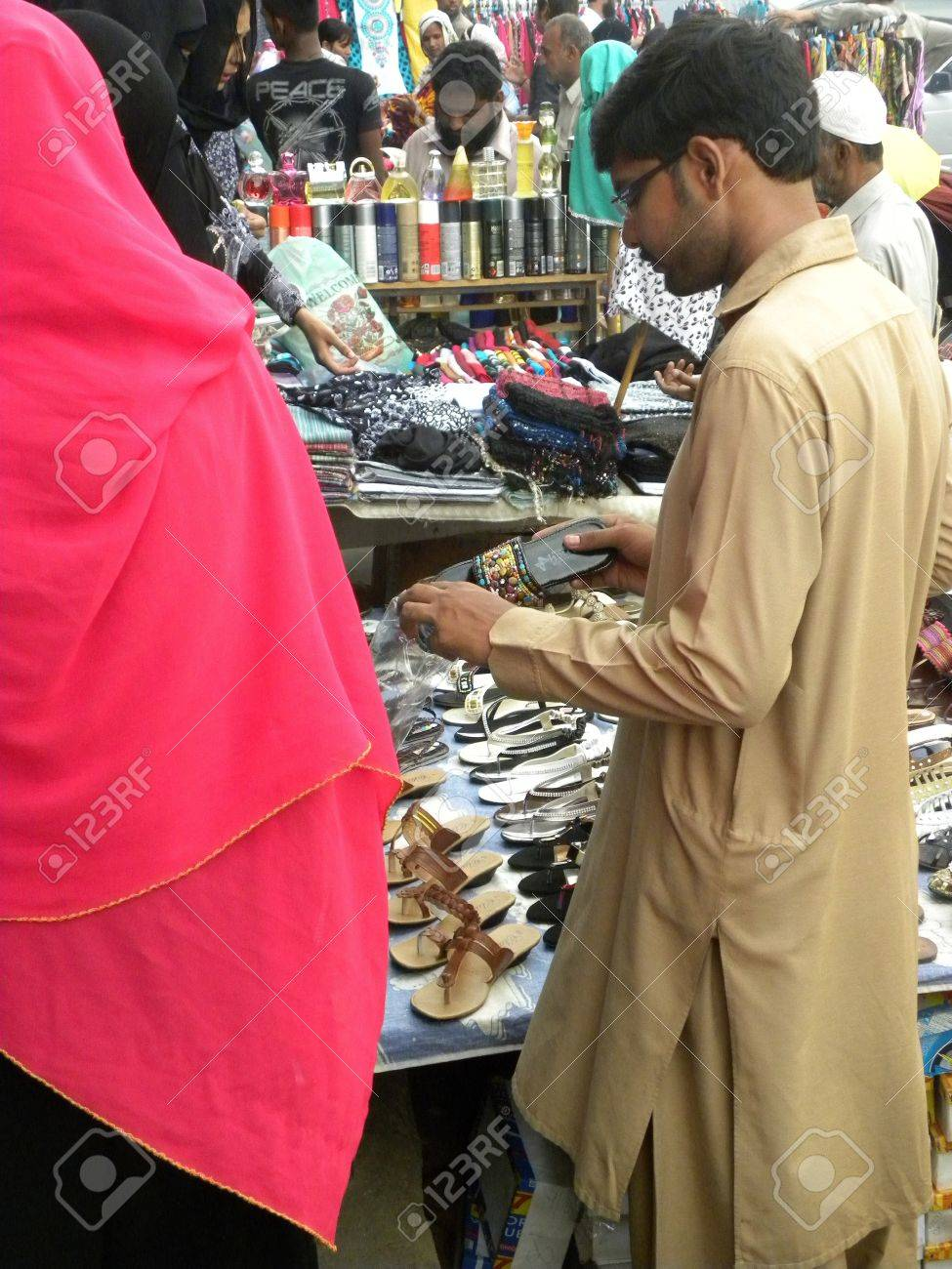 Plastic bag keeper - Pakistan Karachi_shop Keeper Packing The Ladies Shoes In Plastic Bag For Customer Today On Wednesday