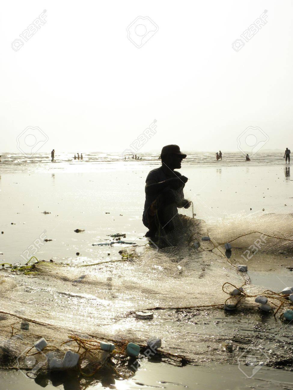 KARACHI PAKISTAN_FISHERMAN COLLECTING FISH FROM FISH NET AT SEA