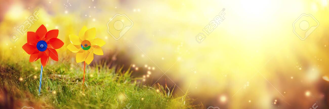 Two orange and yellow pinwheels against nature background in summer morning. Banner. - 124319757