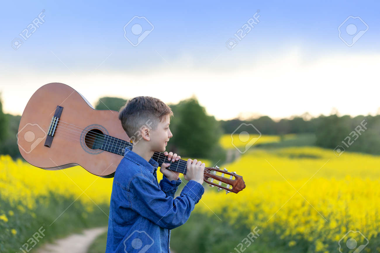 Portrait handsomeboy with guitar walking in the summer yellow field. Young musician on the road to success. - 169813081