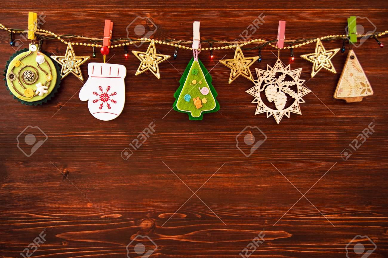 Wooden and felt christmas decorations and christmas lights on stock photo wooden and felt christmas decorations and christmas lights on a rope on the brown wooden background top view aloadofball Gallery
