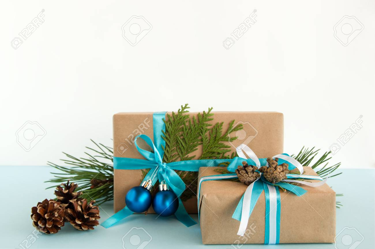 christmas gift boxes wrapped of craft paper blue and white ribbons decorated of fir