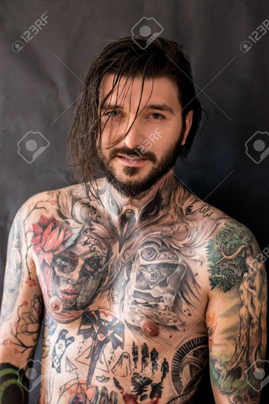 tattooed naked man with messy wet hair on black background stock