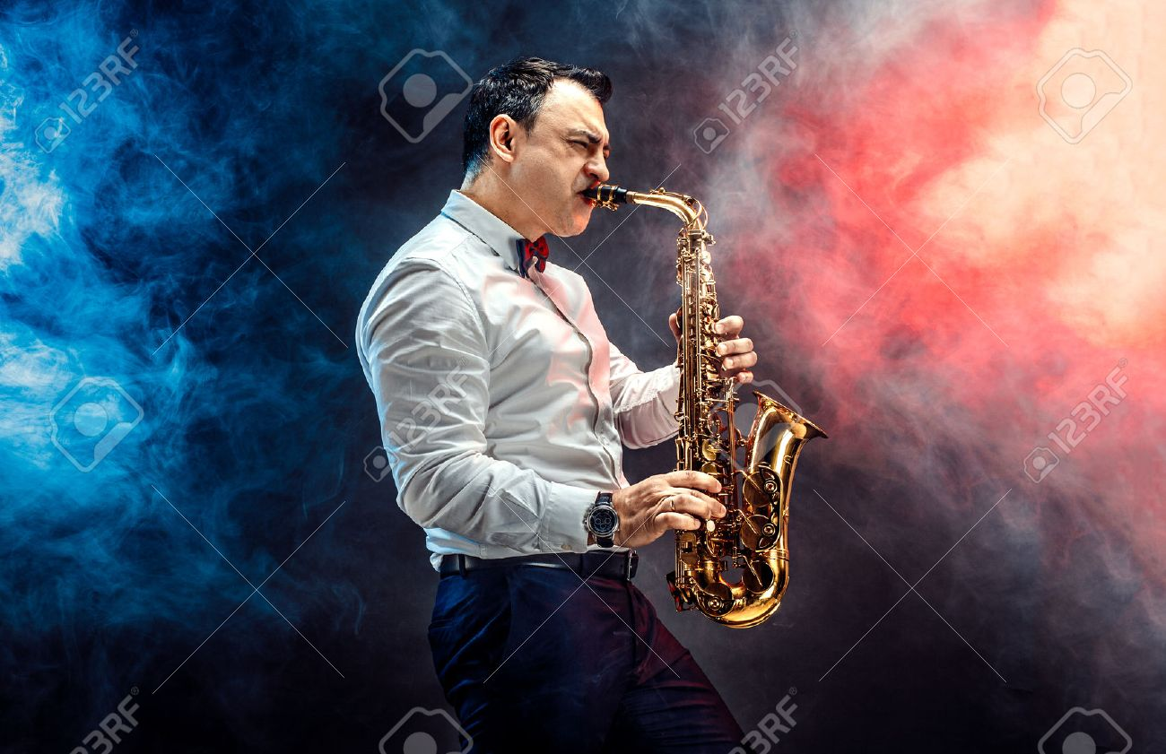 Elegant saxophonist plays jazz on dark background in a smoke Stock Photo - 56015350