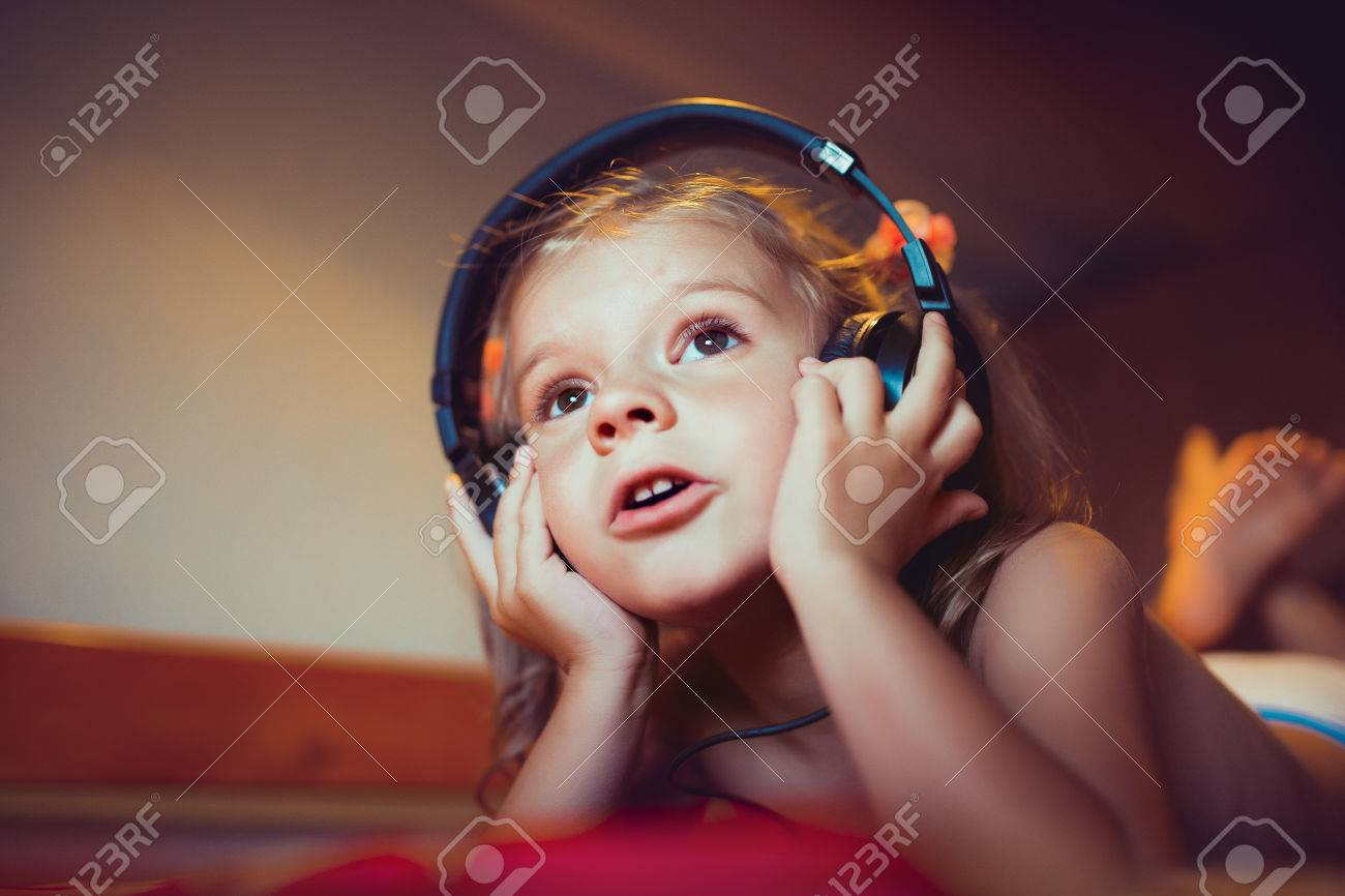 Cute little kid listening music lying on bed at home - 60303682