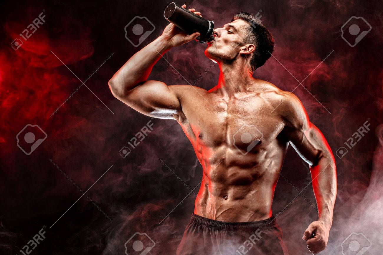 Muscular man with protein drink in shaker over dark smoke background - 68653349