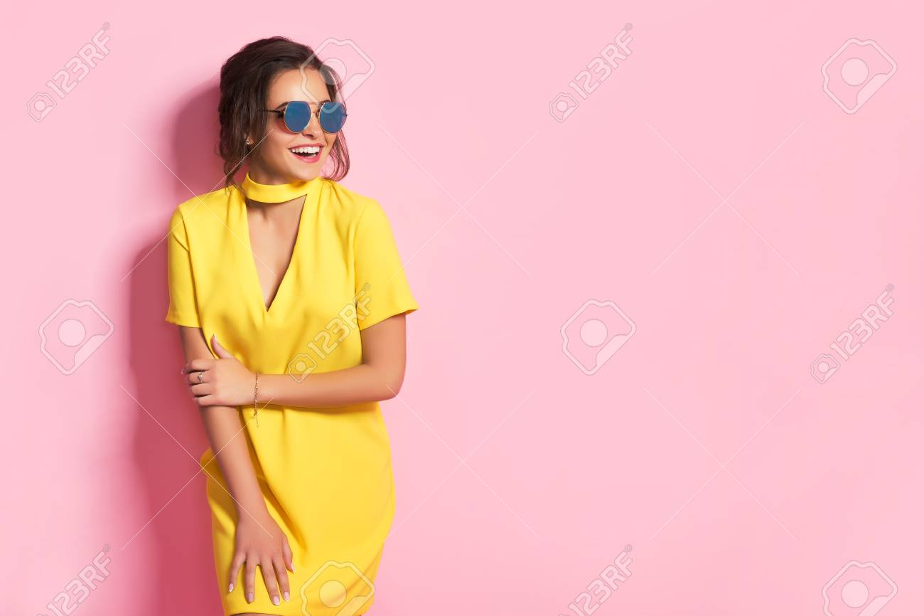 Beautiful girl in colorful clothes wearing sunglasses posing on pink background in studio. - 78750097