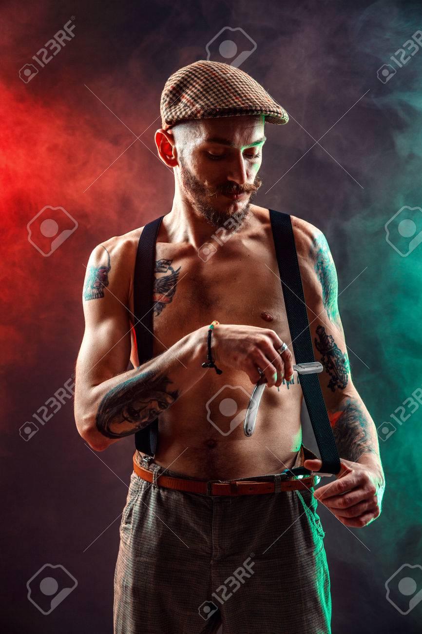 Stylish tattooed shirtless barber gangsta man with razor looking at camera. - 80326194