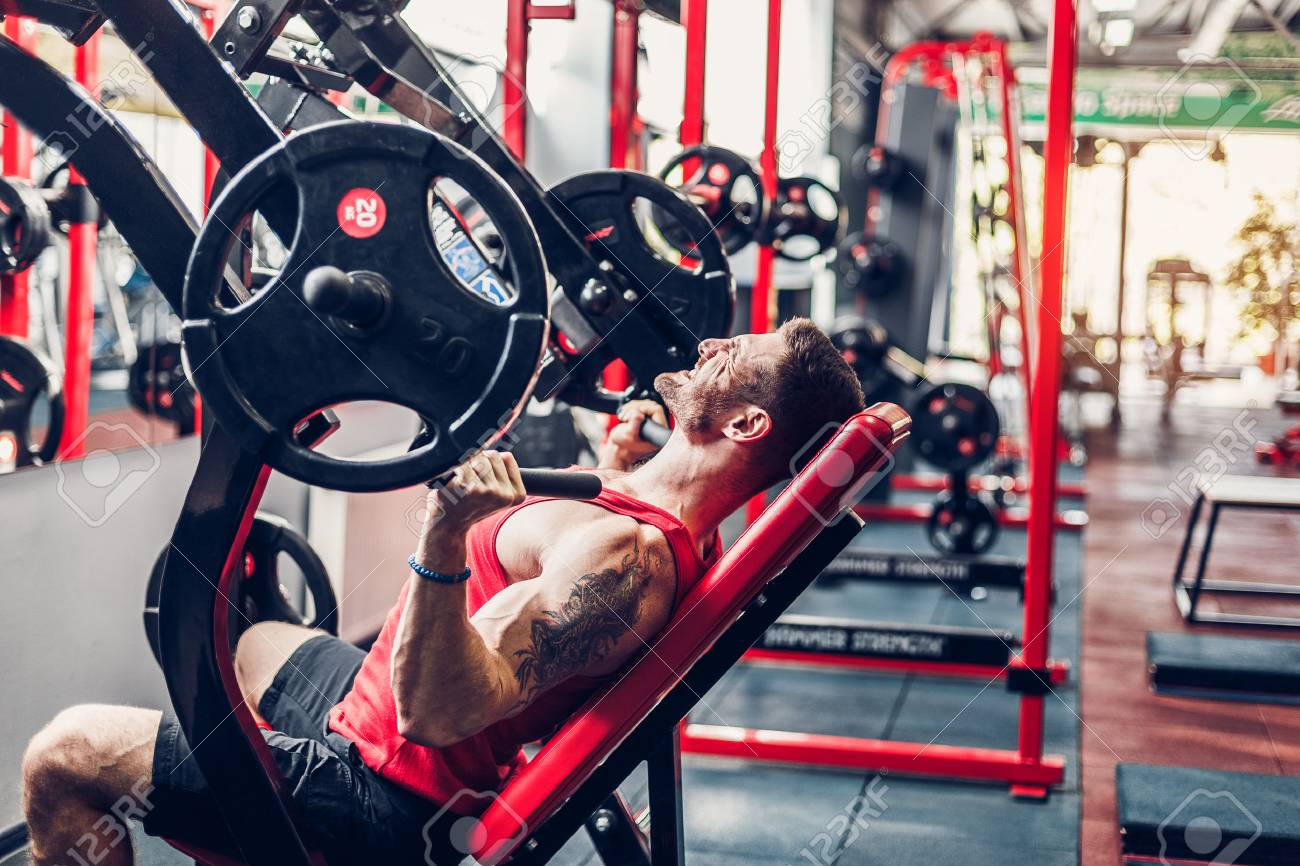 Sports guy doing exercise for the shoulders on the simulator in the gym. Brutal sports man. Bodybuilder on training in the gym. Health and fitness - 84430820