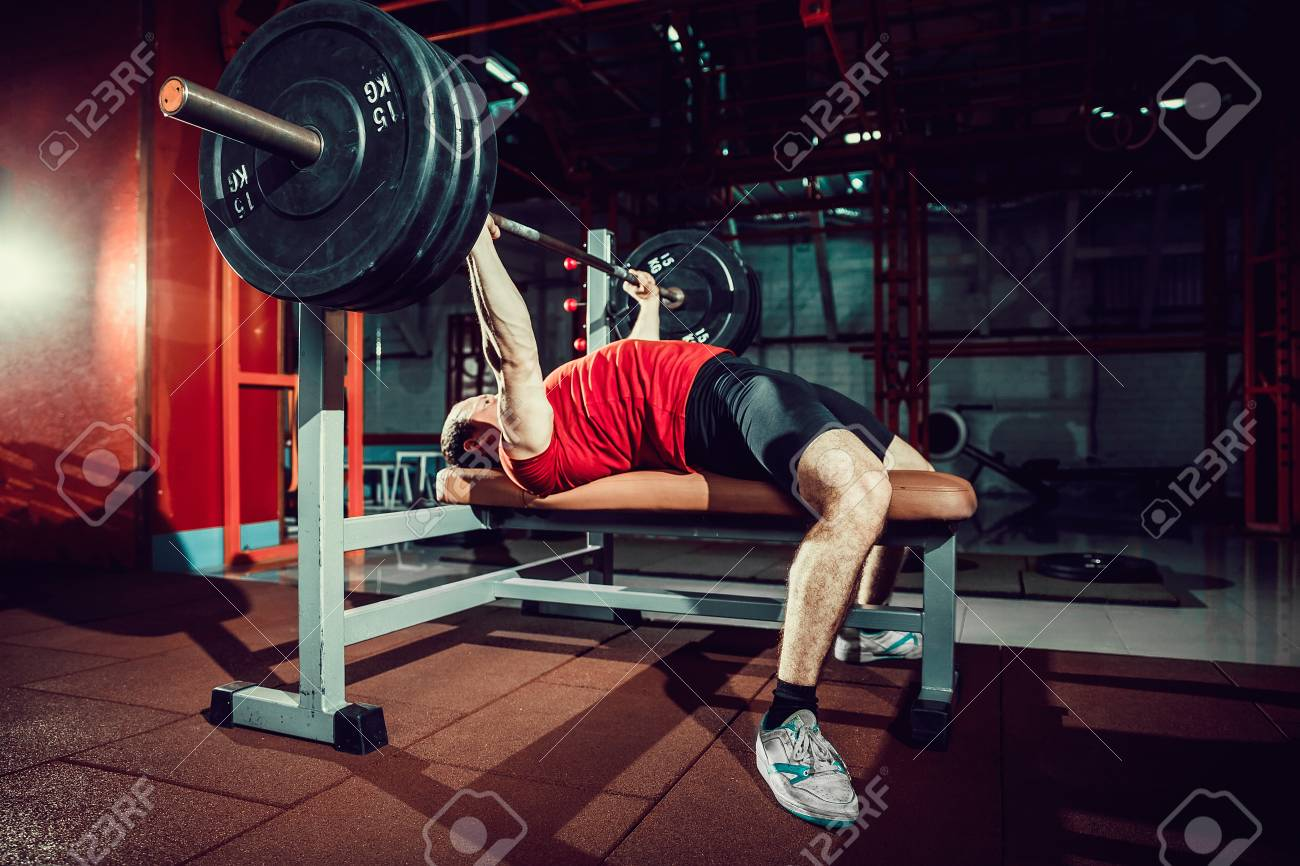 Very Strong man doing bench press workout in gym. - 93694691