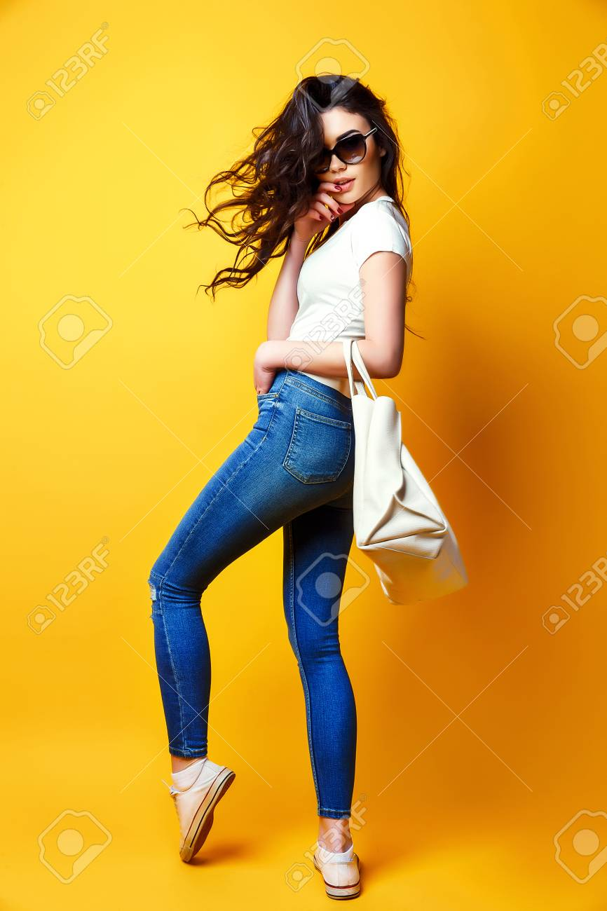 Beautiful young woman in sunglasses, white shirt, blue jeans posing with bag on the yellow background - 95851548