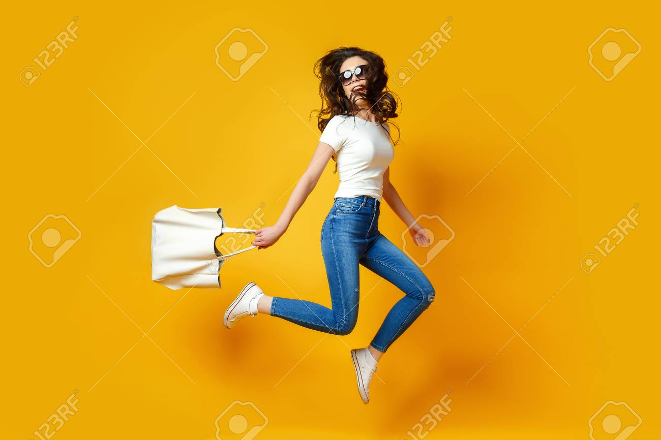 Beautiful young woman in sunglasses, white shirt, blue jeans posing, jumping with bag on the yellow background - 95851549