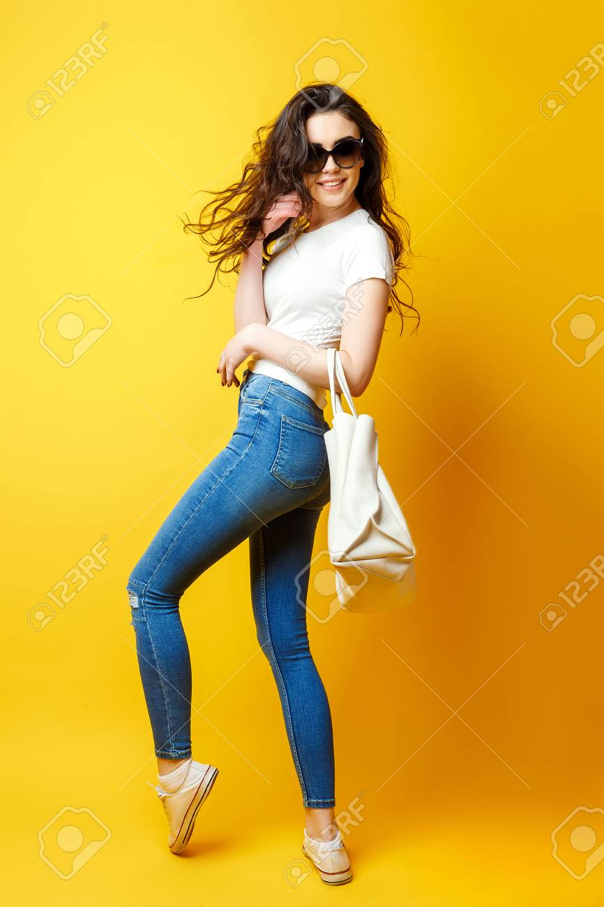 Beautiful young woman in sunglasses, white shirt, blue jeans posing with bag on the yellow background - 96155016