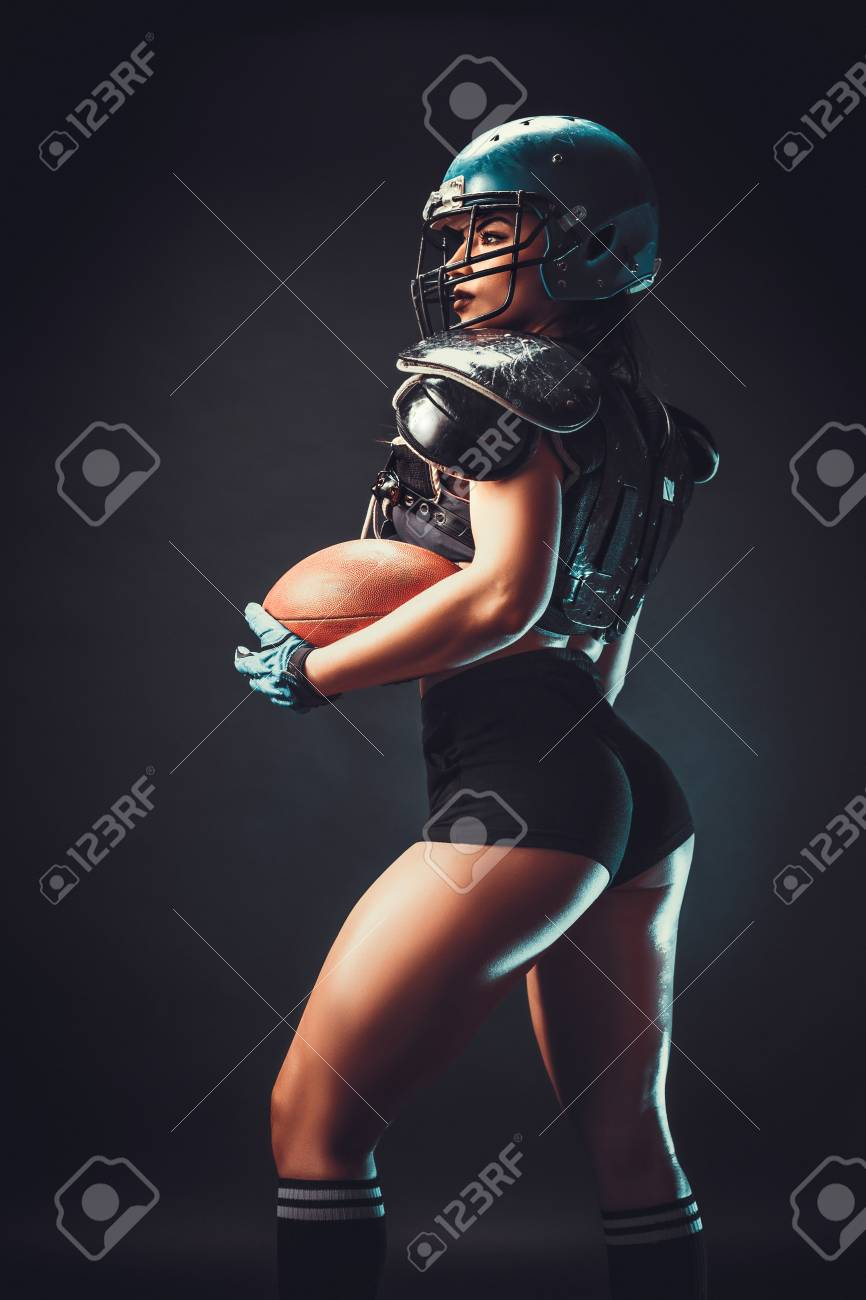 Sportive serious woman in helmet of rugby player holding ball in stuio on dark background. - 97098071
