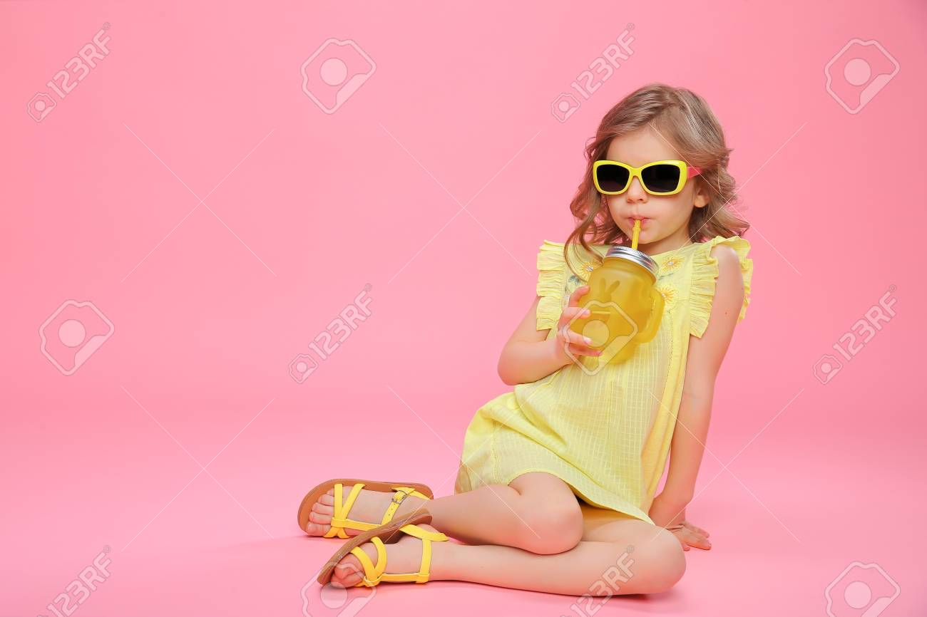 Pretty little girl in dress and sunglasses sitting on pink with glass jar of cocktail chilling. - 100151735