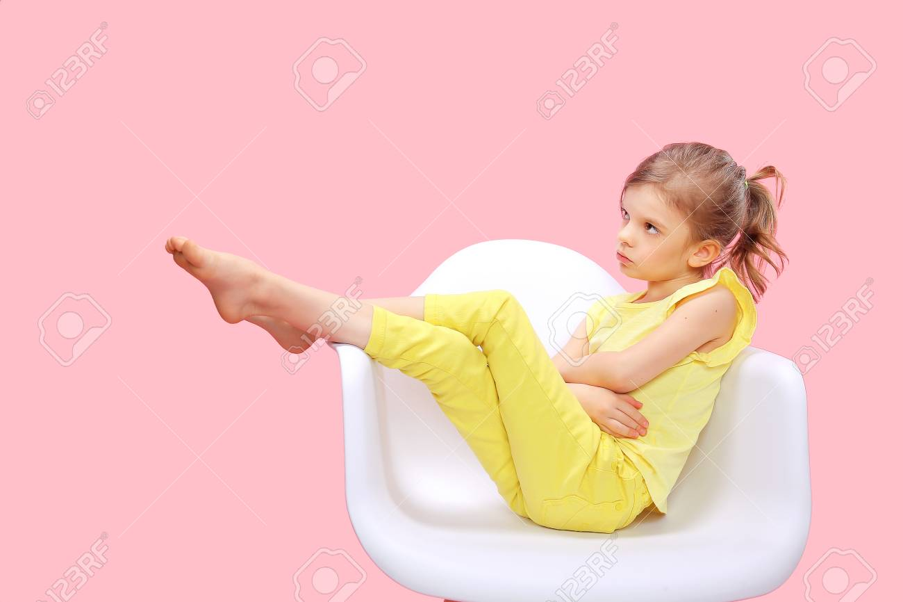 Dreaming Stylish little girl in yellow clothes sitting and posing in chair on pink background. - 100397961