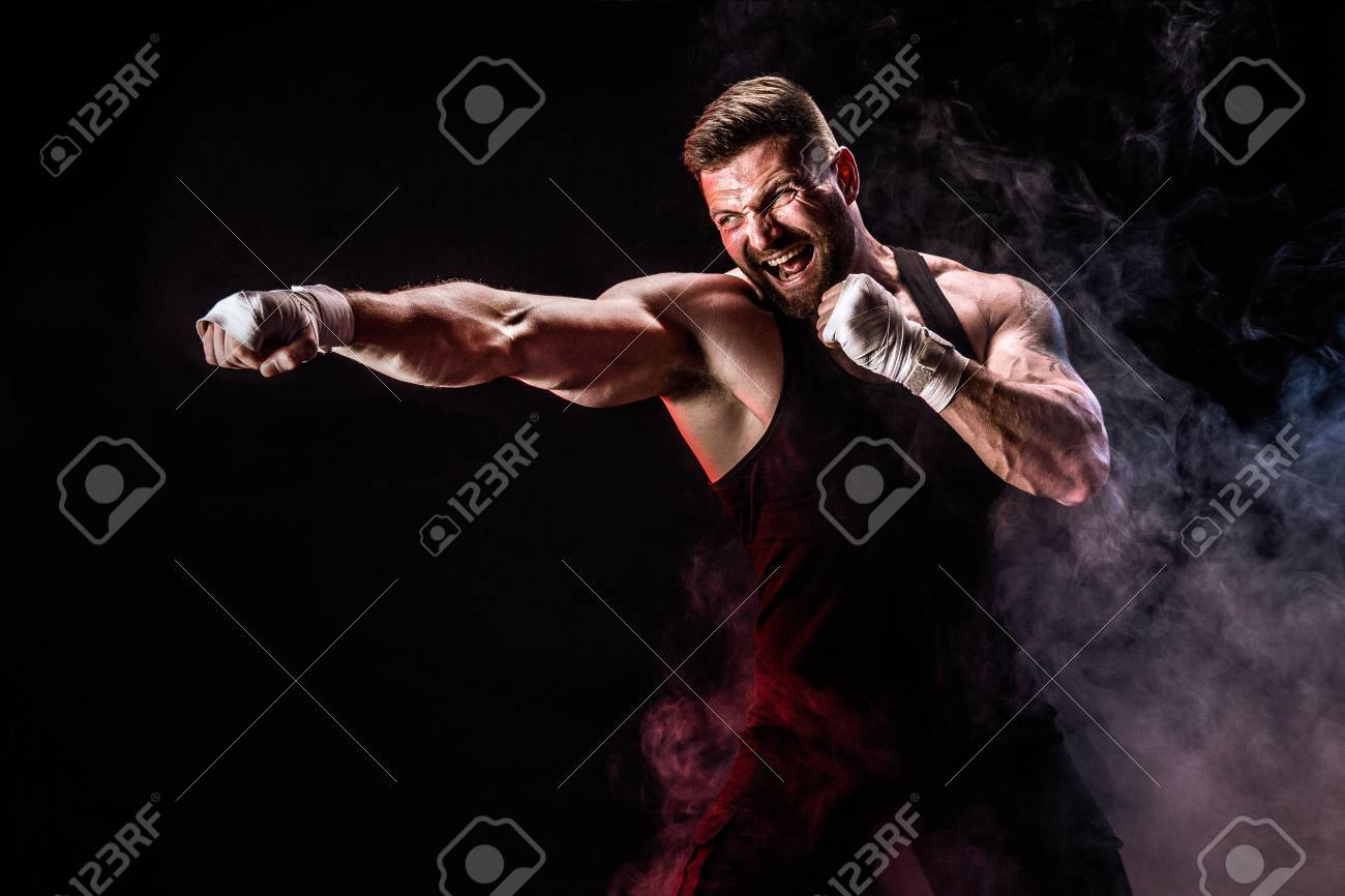 Sport concept. Sportsman muay thai boxer fighting on black background with smoke. Copy Space. - 100899741