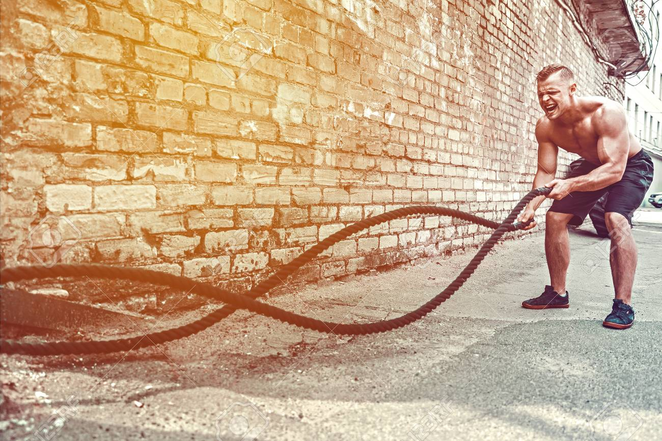 Athletic man working out with rope in front of brick wall. Strength and motivation. Outdoor workout. - 105505042