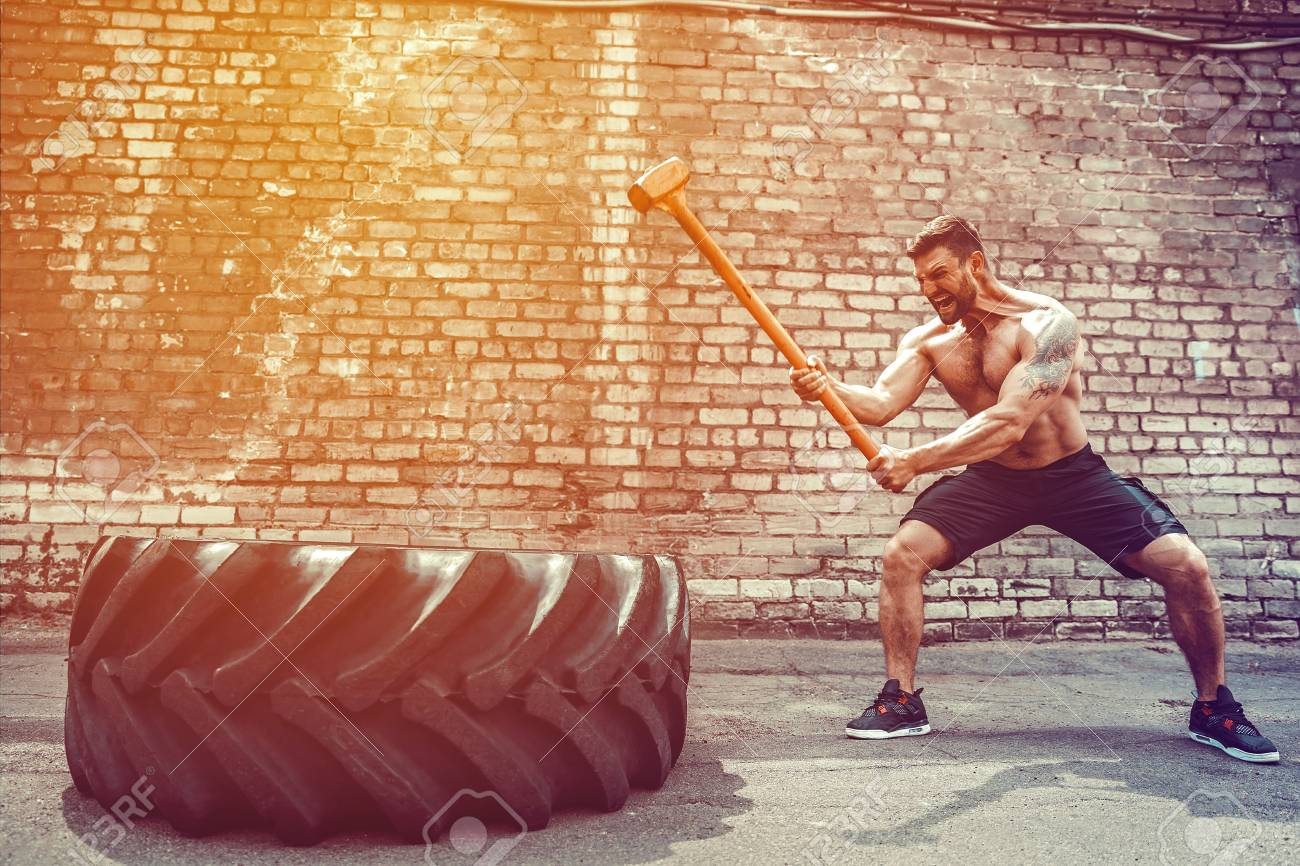 Sport Fitness Man Hitting Wheel Tire With Hammer Sledge Crossfit Training, Young Healthy Guy Gym Interior OUTSIDE - 105789203