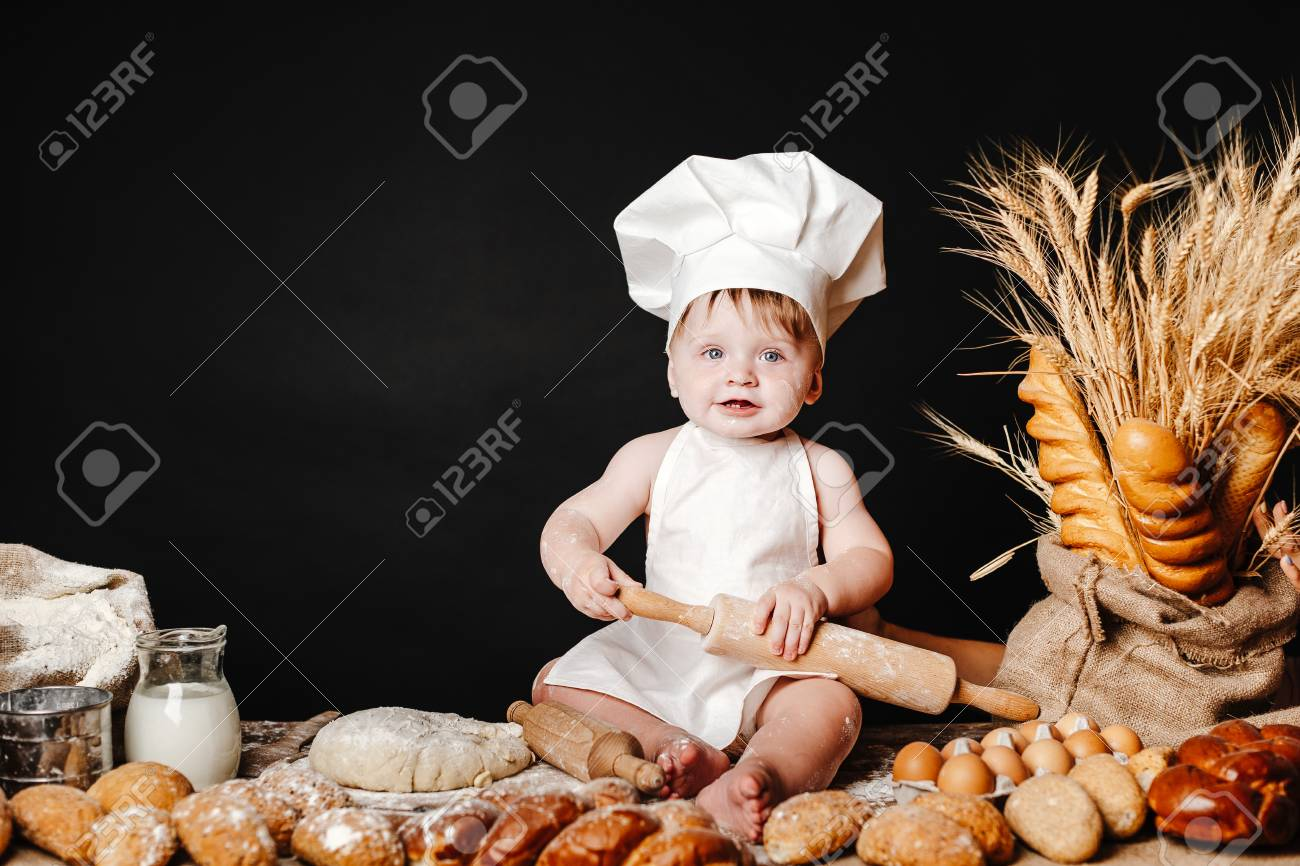 Charming toddler baby in hat of cook and apron sitting on table with bread loaves and cooking ingredients laughing happily - 106222740
