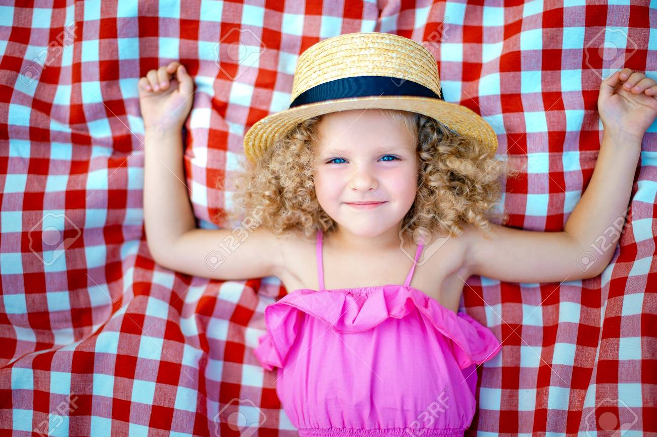 892f53e06ee Small curly-haired girl in a straw hat lies on a checkered carpet on the