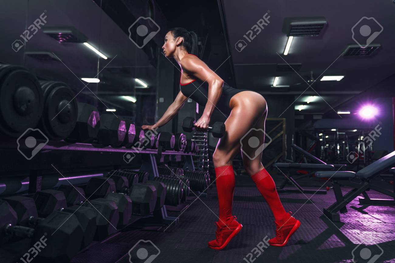 Attractive fit woman in the gym crouches with a barbell. Woman training back. Colored smoke - 121071439