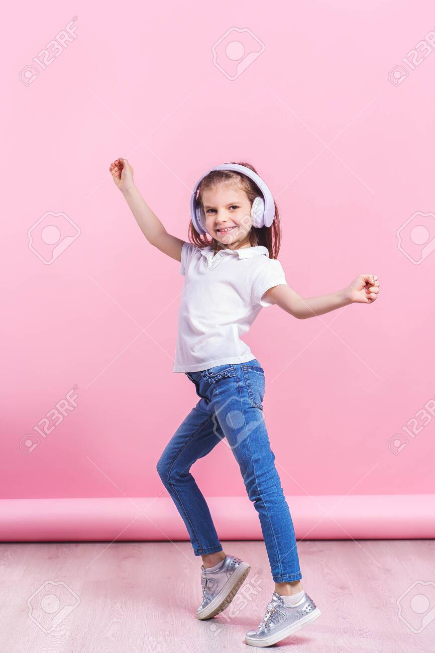 Girl listening to music in headphones an dance. Cute child enjoying happy dance music, smile, posing on pink studio background wall. - 122352867