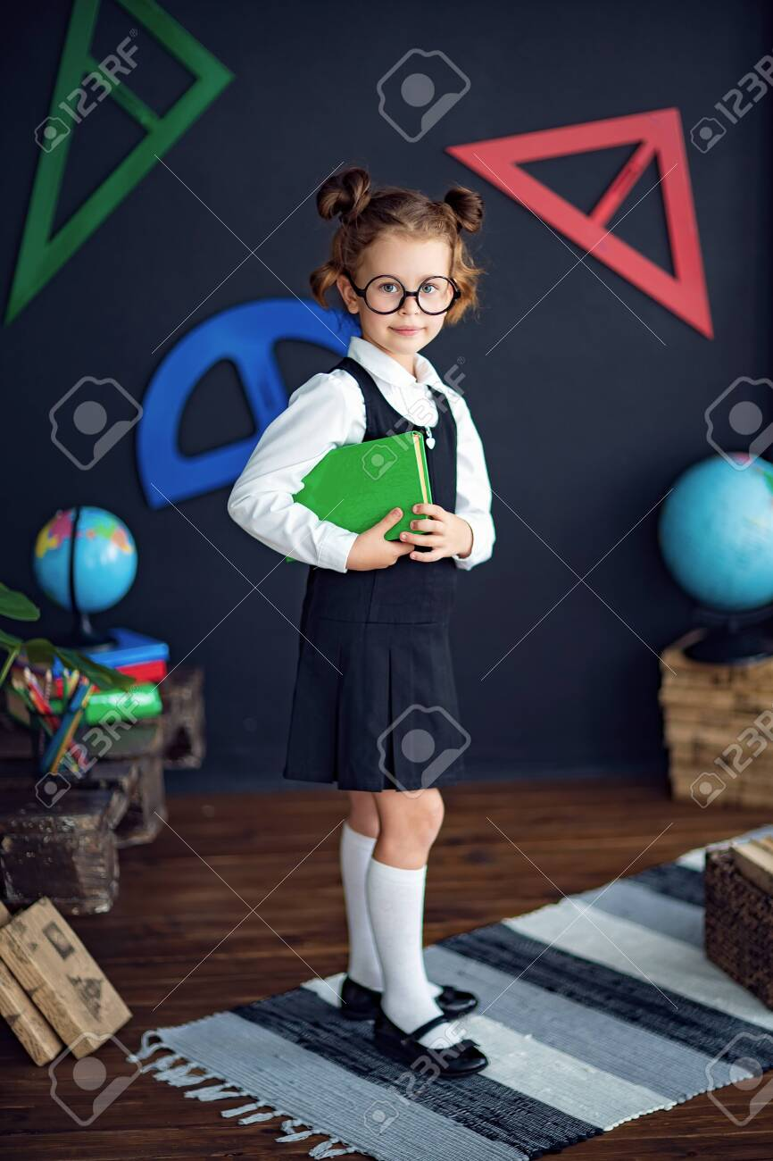 Clever little girl in school uniform and glasses smiling and looking at camera while holding green textbook before studies - 132323181