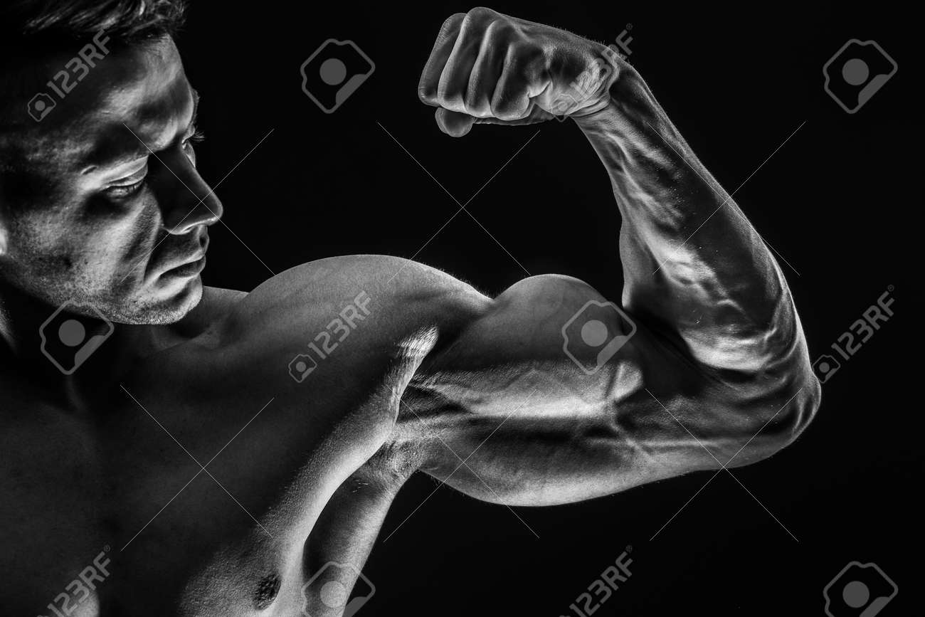 Strong Athletic Sexy Muscular Man on Black Background showing biceps - 168108036