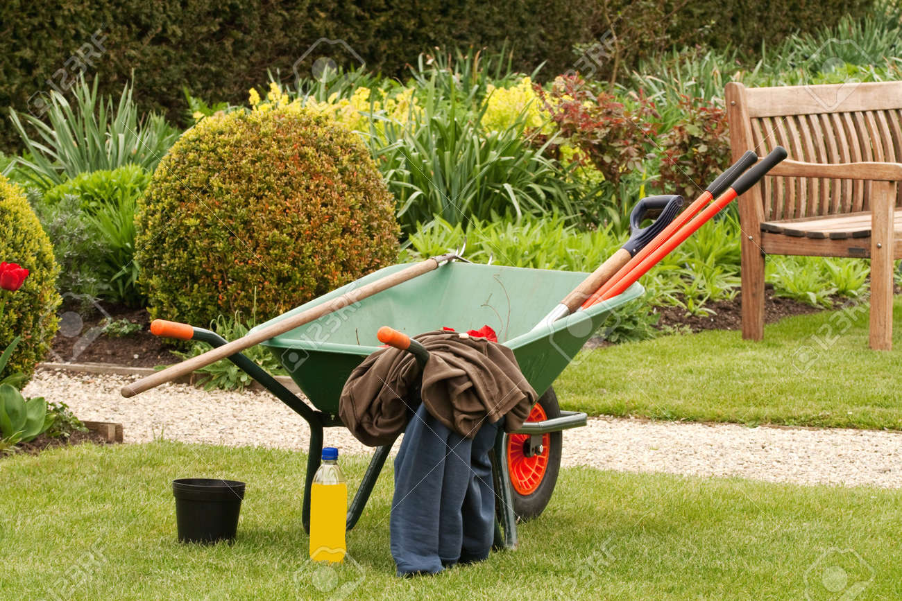 Delightful Wheelbarrow In A Garden With Clothes And A Bottle Of Drink Stock Photo    4701499