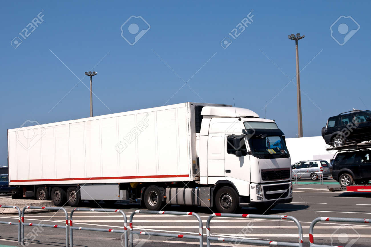 Large lorry driving past a car transporter as it leaves the ferry Stock Photo - 19598688