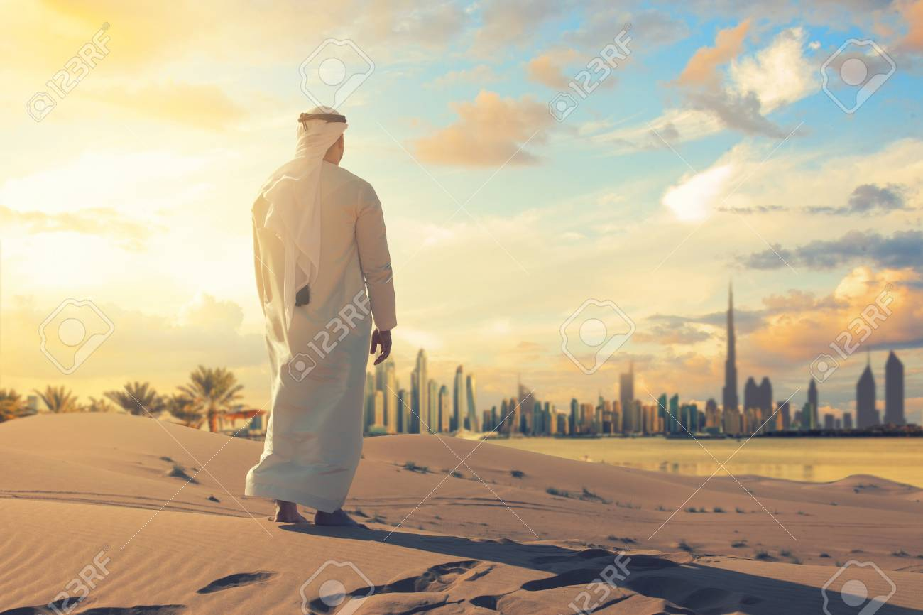 Arabic man with traditional emirates clothes sitting on kness