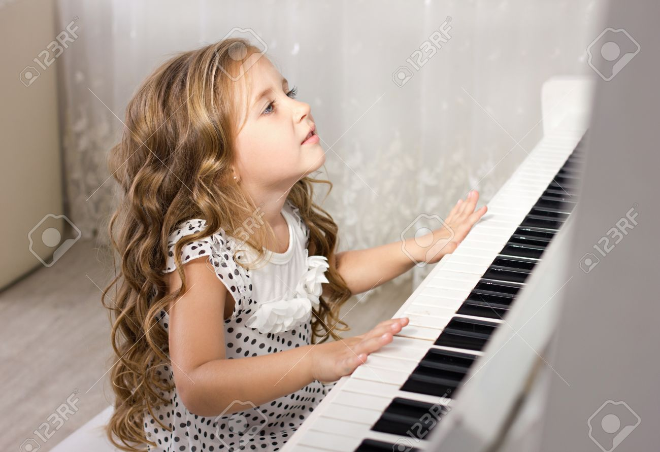 beautiful blond little girl playing near a piano in a white room Stock Photo - 14853437