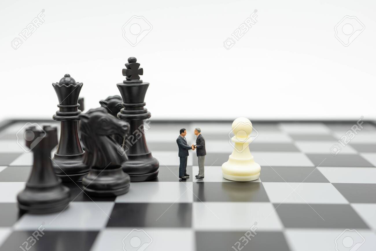 Miniature 2 people businessmen Shake hands standing on a chessboard with a chess piece on the back Negotiating in business. as background business concept and strategy concept with copy space. - 130119151