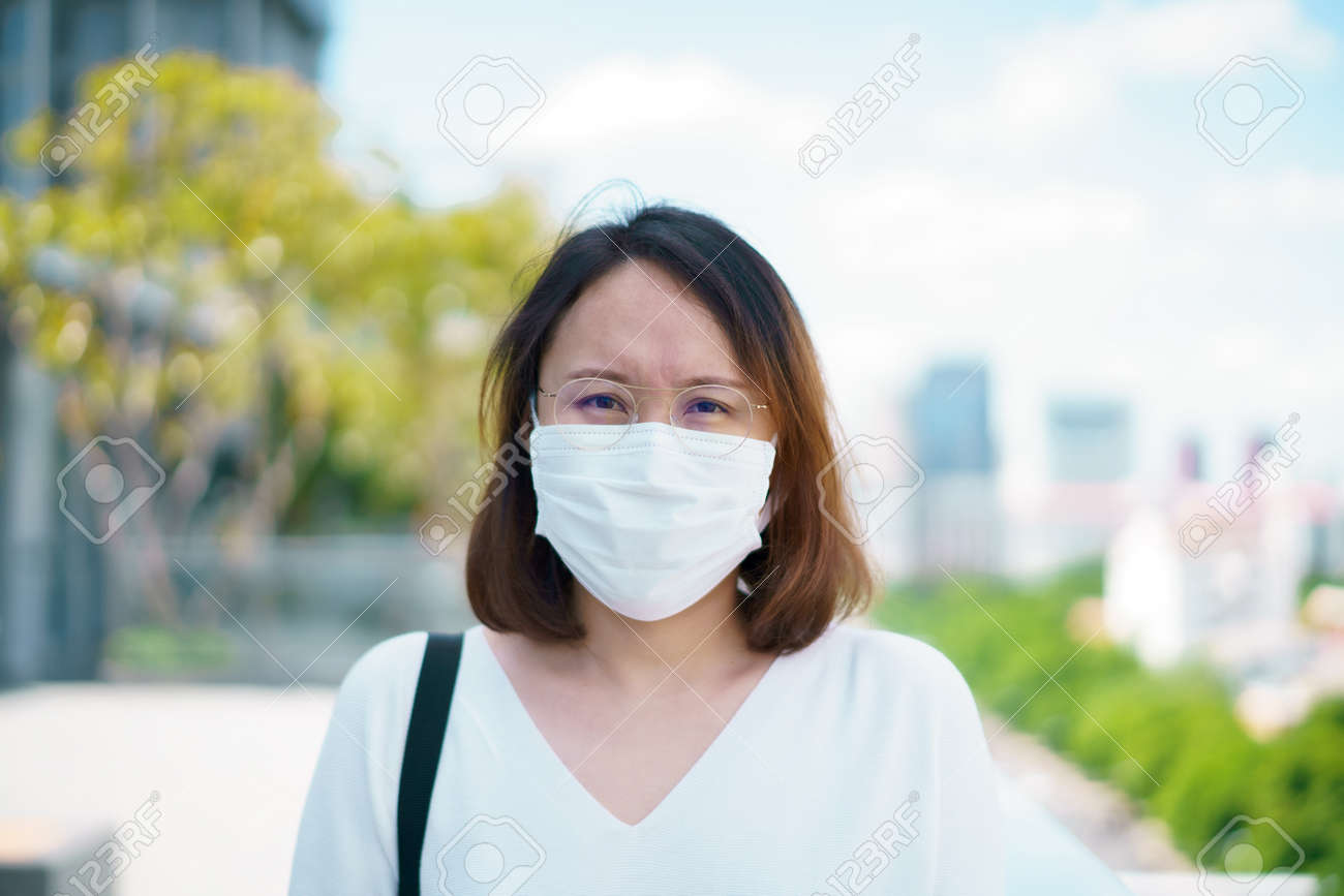 Woman wearing face mask protect filter against air pollution (PM2.5) or wear N95 mask. protect pollution, anti smog and viruses, Air pollution caused health problem. environmental pollution concept. - 170694814
