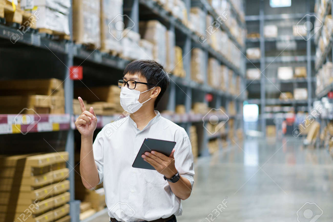 Portrait Asian men, staff, product counting Warehouse Control Manager Standing, counting and inspecting products in the warehouse - 171394281